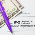 W-2 forms, purple pen, and $100 bill | CTR Payroll Pittsubrgh